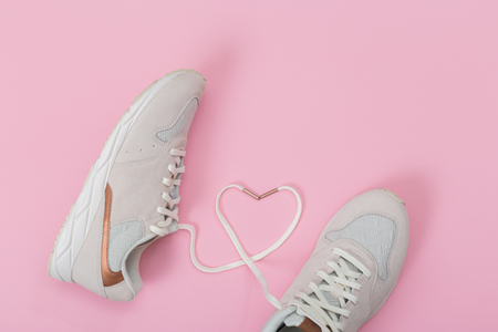 blonde sneakers on a pink background.Fashion Trendy Trainers with Heart. Love, Hipster Set. Female sneakers, sport shoes in flat lay style, top view.