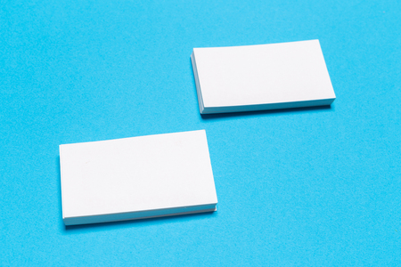 Blank white business cards on blue background. Mockup for branding identity. Template for graphic designers portfolios. Top view. Reklamní fotografie