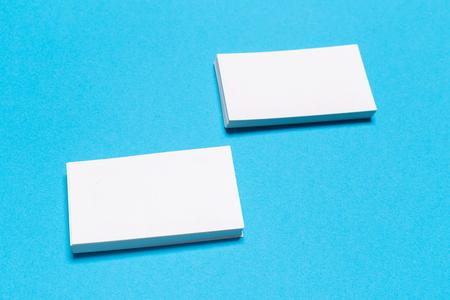 Leere weiße Visitenkarten auf blauem Hintergrund. Mockup für Markenidentität. Vorlage für Grafikdesigner-Portfolios. Ansicht von oben. Standard-Bild