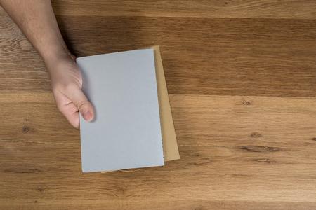 Mano que sostiene la maqueta de la hoja de papel en blanco blanco sobre fondo de madera. Brazo en camisa sostenga la plantilla de folleto claro simulacro. Diseño de la superficie del documento de folleto. Espectáculo de pantalla de impresión pura simple. Lectura de acuerdo de contrato.