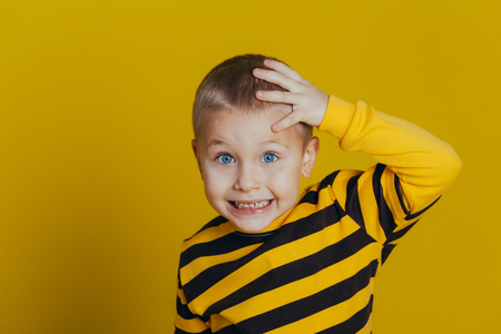 Portrait of an attractive thoughtful boy in a striped sweater holding a hand on his head close-up, on a yellow background Stock Photo