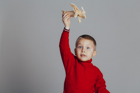 Portrait of attractive boy in red sweater playing with wooden plane close-up, on gray background 스톡 콘텐츠