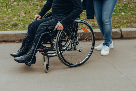 Close-up of a male hand on a wheel of a wheelchair during a walk in the park. Walk in the afternoon together in the park