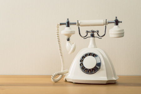 Vintage old white telephone on wooden table with color wall background Banque d'images