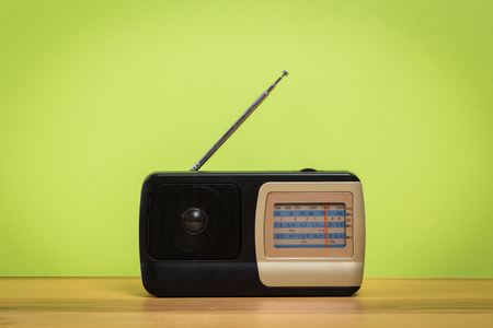 Vintage old radio on wooden table with color wall background Reklamní fotografie