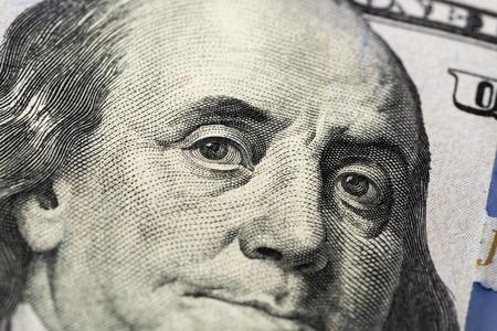 Dollars américains. Une pile de billets de cent dollars. Gros plan du nouveau billet de cent dollars sur fond blanc.