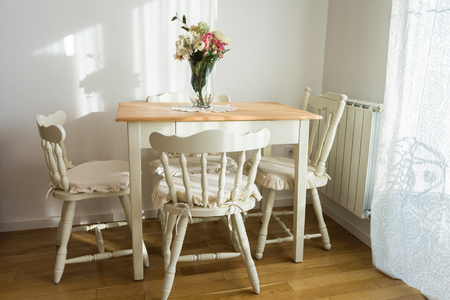 Ładnie urządzony salon (obiadowy) pokój. Stół i kilka krzeseł.