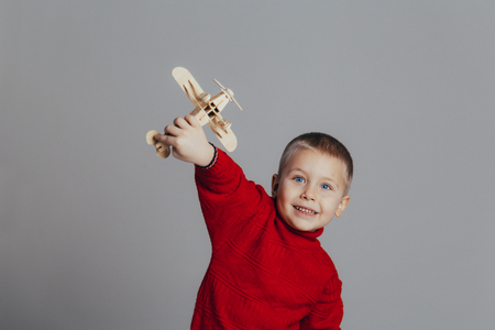 Portrait of attractive boy in red sweater playing with wooden plane close-up, on gray background