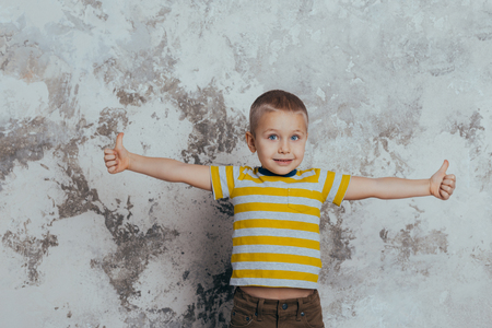 Young boy child in a yellow striped T-shirt celebrating a happy smiling laugh with a hand spread over a gray background