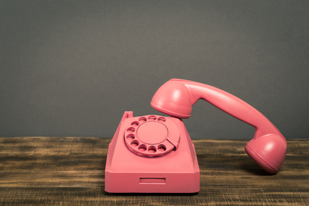 Vintage old pink telephone on wooden table with color wall background
