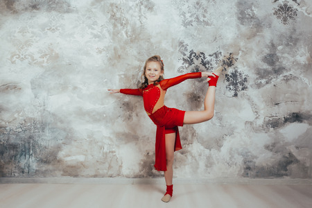 Girl gymnast in a red gymnastic swimsuit posing on studio background. practicing gymnastic