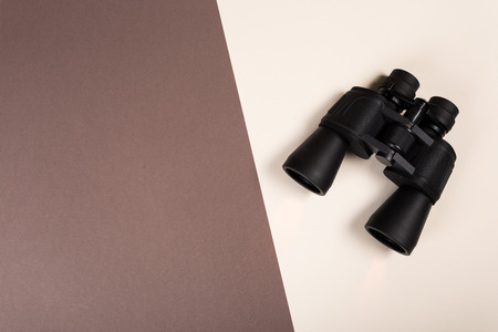 Black binoculars with orange lens on pastel background