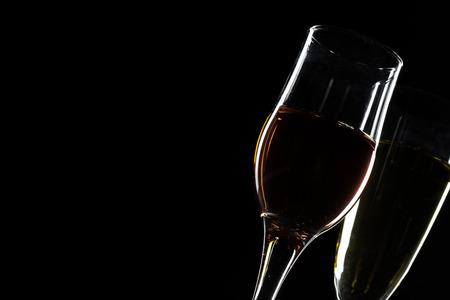 黒い背景の上に赤、バラ、白ワインのグラス。ワインカードメニューデザイン。ワインテイスティング用高級ワインとワイングラスのクローズアップ 写真素材