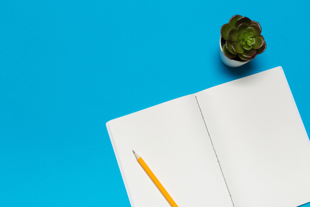 Blank paper notebook on blue background.Office desk table concept.