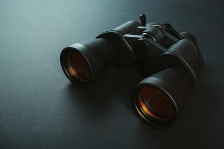 Schwarzes Fernglas mit oranger Linse auf dunklem Hintergrund