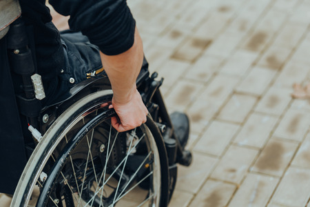 Primo piano della mano maschile sulla ruota della sedia a rotelle durante la passeggiata nel parco. Tiene le mani sul volante. Archivio Fotografico