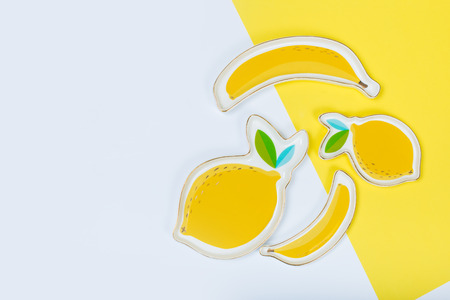 banana-like plate and limon plate on yellow background. concept