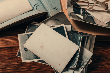Stack old photos on table. Mock-up blank paper. Postcard rumpled and dirty vintage. Retro card