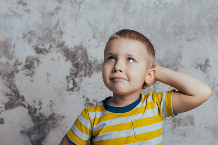 Portrait of a thoughtful cute little child with hand touching face, no  looking at camera against concrete wall background