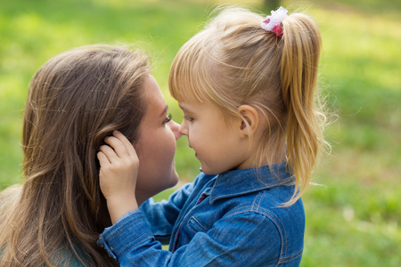 little happy girl hugs her mom and tells her something in the ear in the park