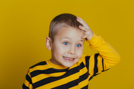 Portrait of an attractive thoughtful boy in a striped sweater holding a hand on his head close-up, on a yellow background Reklamní fotografie