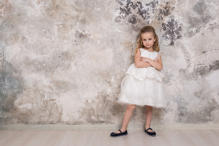 Portrait of a little attractive smiling girl in a white dress with curled hair against the background of a grunge wall. Studio shot with space for text.