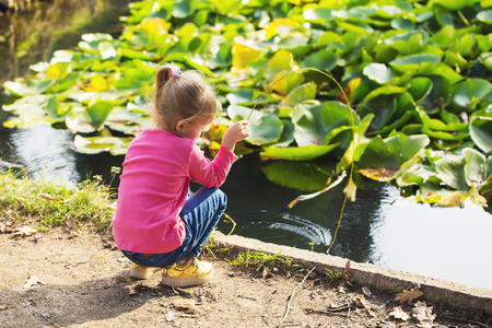 little girl in a pink blouse plays in the park by the pond