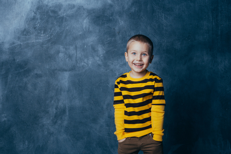 Little fashionable boy posing in front of a gray-blue concrete wall. Portrait of a smiling child dressed in a black and yellow striped sweater and brown pants.