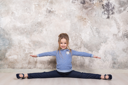 Portrait of a little attractive smiling girl in a blue sweater and pants with her hair folded in her hair sitting on a string against the background of a grunge wall. Studio shot with place for text, fashion concept