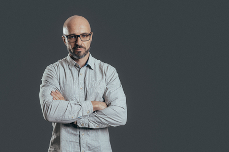 Serious middle aged man with a deadpan face with folded arms expression dressed in casual posing on a dark gray background with copy space