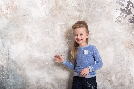 Portrait of a little attractive smiling girl in a blue sweater and pants with hair folded into her hair against a grunge wall background. Studio shot with place for text, fashion concept