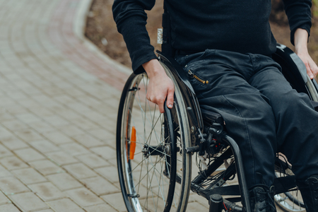 Close-up of male hand on wheel of wheelchair during walk in park. He holds his hands on the wheel. Reklamní fotografie