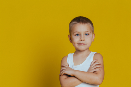 Portrait of an attractive smiling boy in a white T-shirt, arms folded close up, on a yellow background