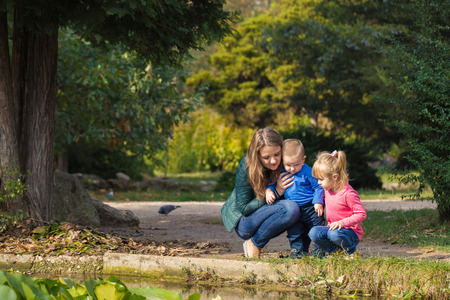 mother plays with her daughter and son in the park by the pond. happy and friendly family