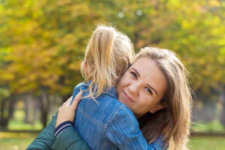 happy mother playing with her daughter hugging her in the park on a summer day Reklamní fotografie