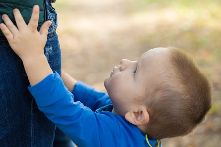 portrait of a little boy wearing a blue jacket touching his mom on a sunny day in the park