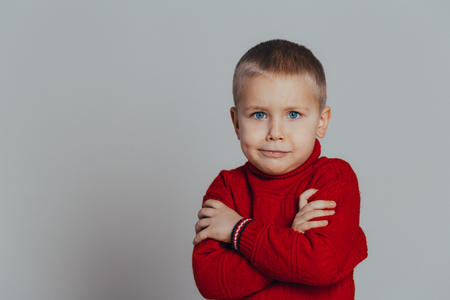 Portrait of attractive serious boy in red sweater with folded hands close up, on gray background Reklamní fotografie