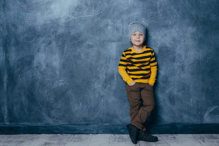 Little fashionable boy posing in front of a gray-blue concrete wall. Portrait of a smiling child in a black and yellow striped sweater and brown trousers. The concept of style and fashion for children. Reklamní fotografie