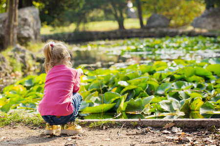 Little girl in a pink blouse plays in the park by the pond Reklamní fotografie