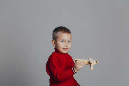 Portrait of attractive boy in red sweater playing with wooden plane close-up, on gray background Reklamní fotografie