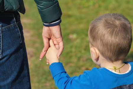 Mother holding a hand of his son in summer day outdoors  in the park