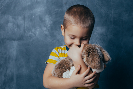 A young emotional boy holds in hands a soft toy dog ​​standing on a blue studio background. Human emotions, facial expression concept. Reklamní fotografie