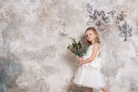 Portrait of a little attractive girl in a white dress with a bouquet in her hands against the background of a grunge wall. Studio shot with space for text. Reklamní fotografie