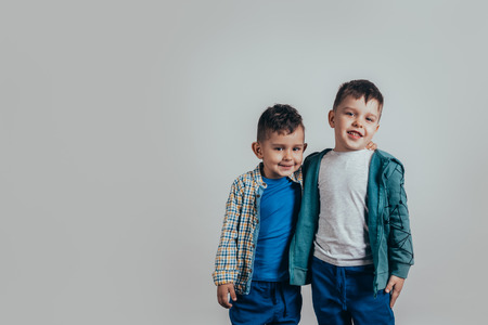 Photo of two adorable boys brothers or friends embracing and smiling joyfully on a gray background. Vintage color