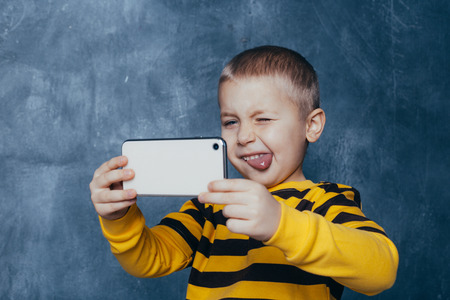 little cute boy with a mobile phone takes a selfie and shows emotions on a blue background Reklamní fotografie