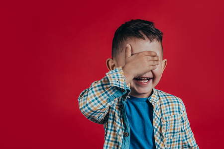 Photo of a charming boy who looks into the camera and closes his eyes with a hand on a red background