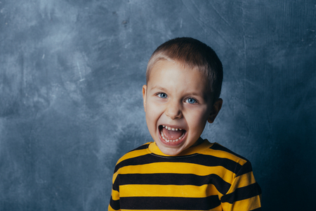 A little boy poses in front of a gray-blue concrete wall. Portrait of a screaming child with open mouth, dressed in a black and yellow striped jacket