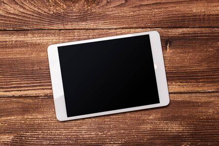 Tableta digital blanca sobre mesa de madera Foto de archivo
