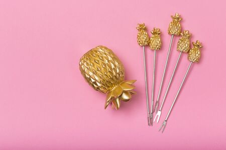 golden pineapple capas on pastel pink background