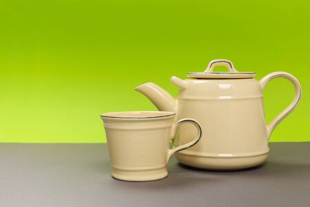 rustic yellow porcelain teapot and cup on a gray board and a green background. 